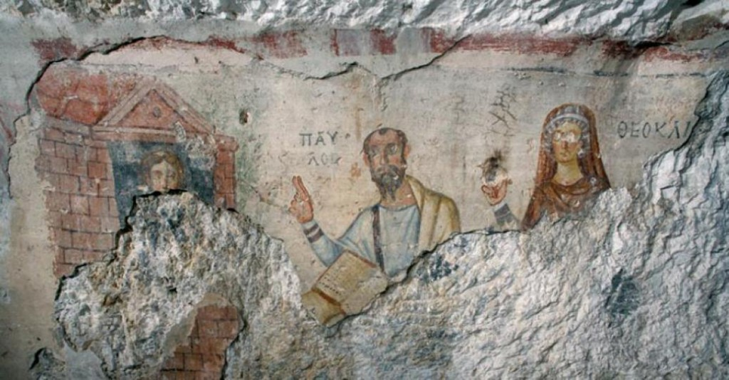 "A wall painting (c. 5th century) depicting a scene from the ""Acts of Paul and Thecla"" wherein Paul and Thecla's mother, Theocleia are both exhorting Thecla, their hands raised in a teaching gesture. Theocleia's eyes and hand have been vandalized."